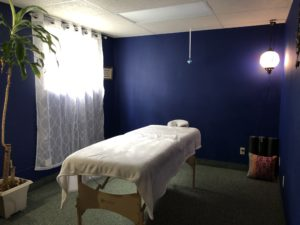 Beautiful Blue room with white massage table and curtians